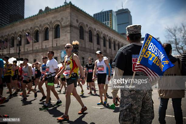 A soldier in the National Guard with a 'Boston Strong' flag cheers on runners as they finish the Boston Marathon on April 21 2014 in Boston...