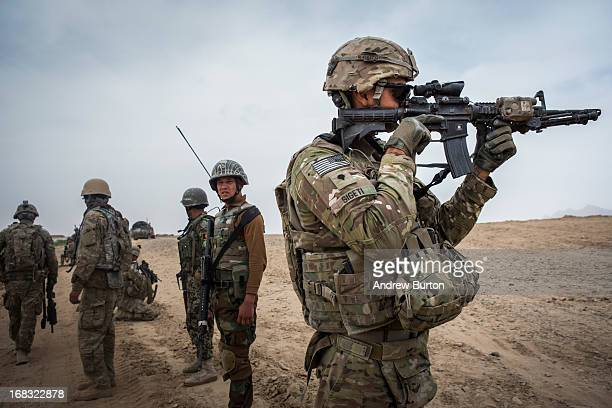 A soldier in the US Army's 1st Battalion 36th Infantry Regiment Charlie Company aims his weapon after a US vehicle hit an improvised explosive device...