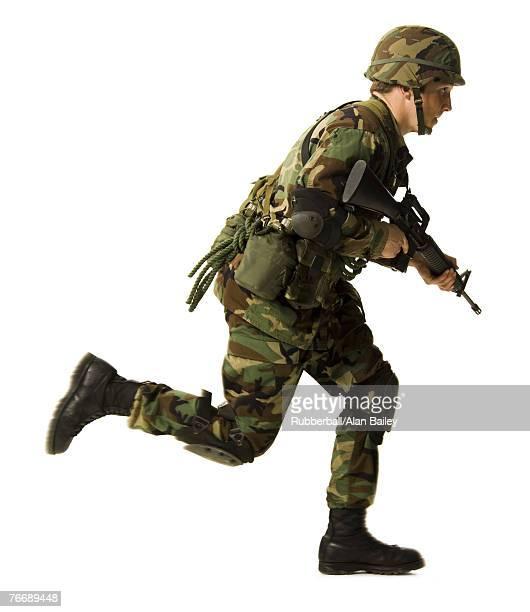 Soldier in uniform with gun running