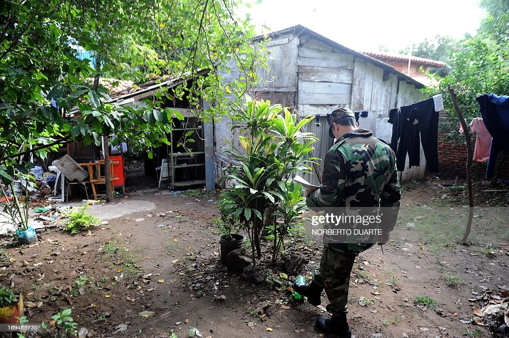 A soldier inspects a house in Asuncion, during an operation to eradicate the Aedes aegypti mosquito, vector of the dengue fever on May 25, 2013. Dengue fever has caused 57 deaths in Paraguay in 2013 . AFP PHOTO/Norberto DUARTE