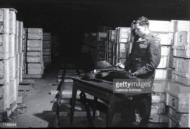 Soldier inspects a priceless violin taken from jews by the Nazi's and stashed in the Heilbron Salt Mines May 3 1945 in Germany The treasures were...