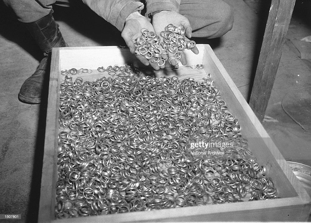 A US soldier inspects thousands of gold wedding bands taken from jews by the Nazi's and stashed in the Heilbron Salt Mines May 3 1945 in Germany The...