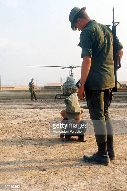 A US soldier is observing with hostility a Viet Cong prisoner hooded and crouched on the ground in the background there is an helicopter US base at...