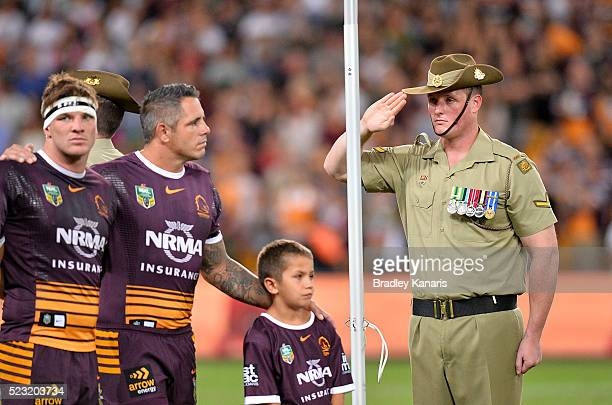 Soldier is seen saluting as players embrace during the playing of the last post in memory of ANZAC Day before the round eight NRL match between the...