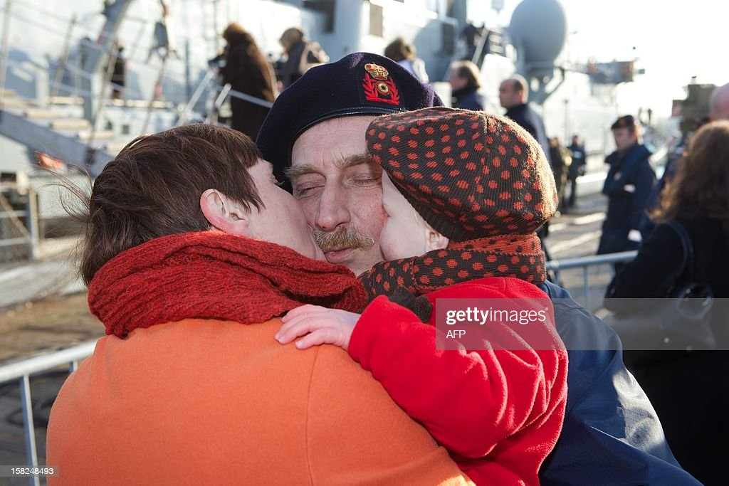 A soldier is welcomed by relatives upon arrival of the Belgian Naval Components Godetia (A960, command and logistical support ship) and Narcis (M923, minehunter) at Zeebrugge naval base, on December 12, 2012. The ships left in August and were part of NATO international excercices and operations SNMCMG1 (Standing NATO Mine Countermeasures Group 1).
