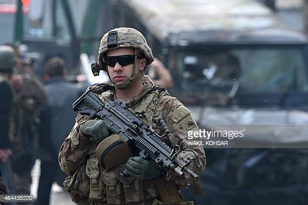 A US soldier keeps watch at the scene following a suicide attack on a Turkish diplomatic vehicle in front of the Iranian embassy in Kabul on February...