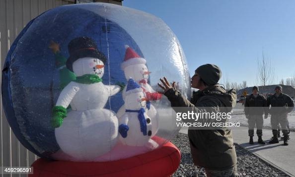 A US soldier kisses an inflatable Snow Dome during Christmas celebration at the US Transit Center of Manas 30 km from Bishkek on December 25 2013 AFP...
