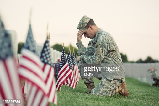 Soldier kneeling at grave