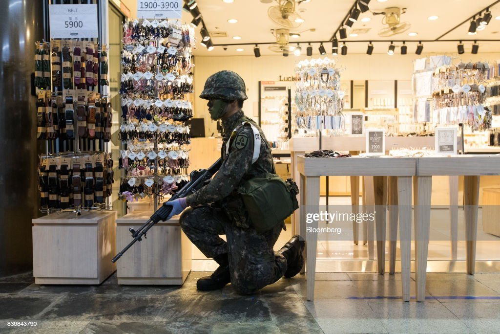 A soldier kneels in front of a jewelry store during an anti-terror drill on the sidelines of the Ulchi Freedom Guardian (UFG) military exercises at a subway station in Seoul, South Korea, on Tuesday, Aug. 22, 2017. North Korea warned the U.S. on Tuesday it will face 'merciless revenge' for ignoring Pyongyangs warnings over annual military drills with South Korea. Photographer: SeongJoon Cho/Bloomberg via Getty Images
