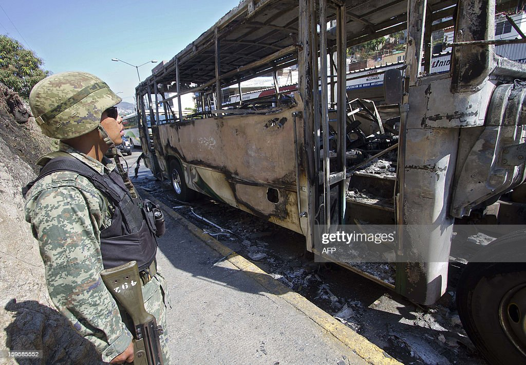 A soldier looks at a bus set ablaze in Mozimba neighborhood, Acapulco, Guerrero State, Mexico on January 16, 2013. The bus was attacked by unkown gunmen who evacuated passengers and killed the driver and his 14-year-old assistant before setting fire to the bus. AFP PHOTO/ Pedro Pardo