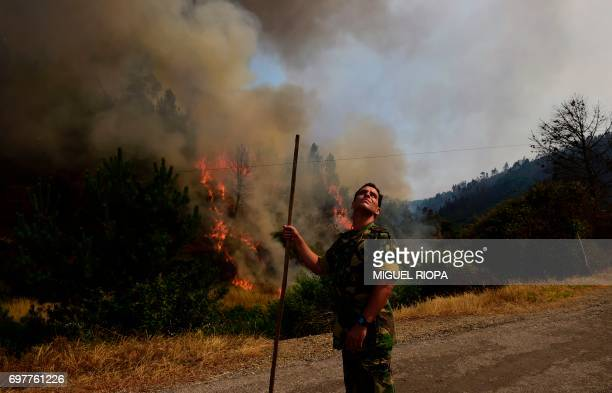A soldier looks at the smoke columns of a wildfire in Carvalho next to Pampilhosa da Serra on June 19 2017 More than 1000 firefighters are still...