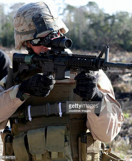 A soldier looks through the scope of a M-4 carbine rifle.