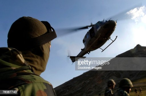 A soldier looks up at a UH-60 Black Hawk helicopter.