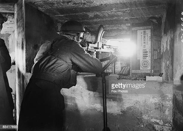 A soldier mans a Bren Gun in a pillbox bunker disguised as a garage and filling station in England during World War II October 1940