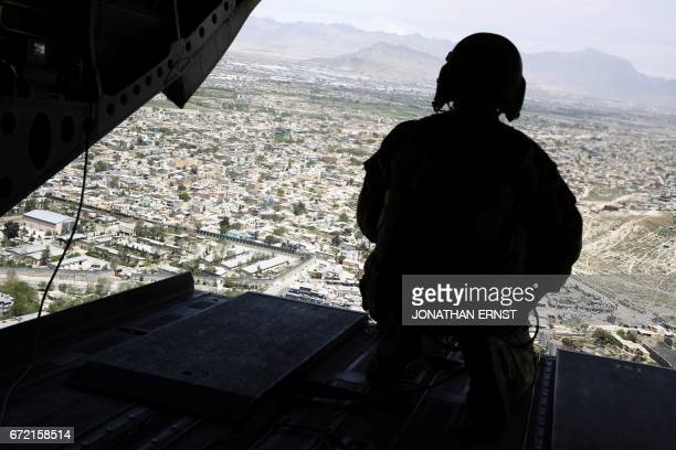 US soldier mans a weapon at the tailgate aboard the helicopter carrying US Defence Secretary James Mattis as he arrives at Resolute Support...