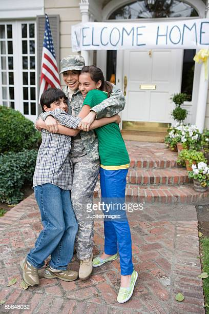 Soldier mother embracing children