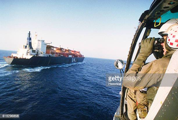 A soldier observes the liquified natural gas carrier Hoegh Gandria from aboard a US Navy SH2F Seasprite helicopter while patrolling the gulf during...