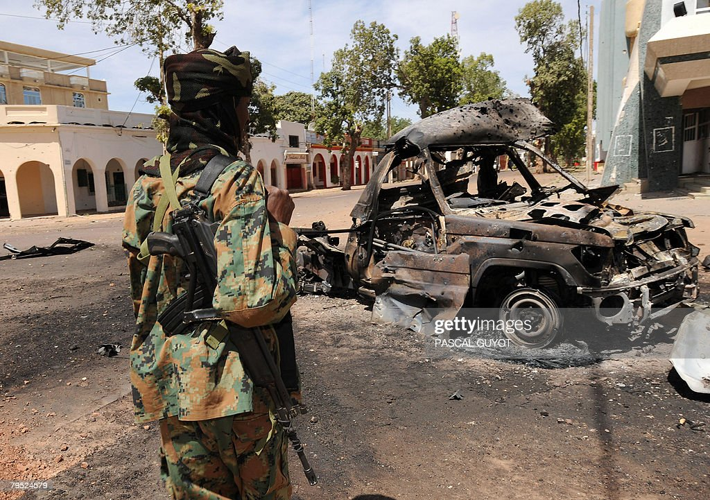A soldier of Chadian army looks at a charred car during a patrol in the capital city N'Djamena on February 05 2008 after a weekend of heavy fighting...