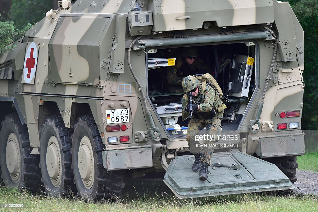 A soldier of the 33rd Panzergrenadier bataillon jumps out of a GTK Boxer AMB armoured ambulance during a drill at the headquarters of the 33rd Panzergrenadier bataillon in Neustadt am Ruebenberge on June 29, 2016. / AFP / JOHN