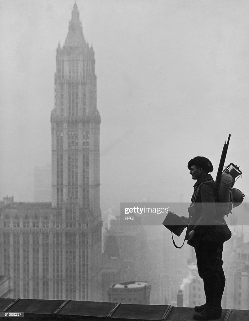 A soldier of the 88th Infantry Division surveys New York from the top of the Equitable Building in Manhattan, circa 1918. On the left is the Woolworth Building.