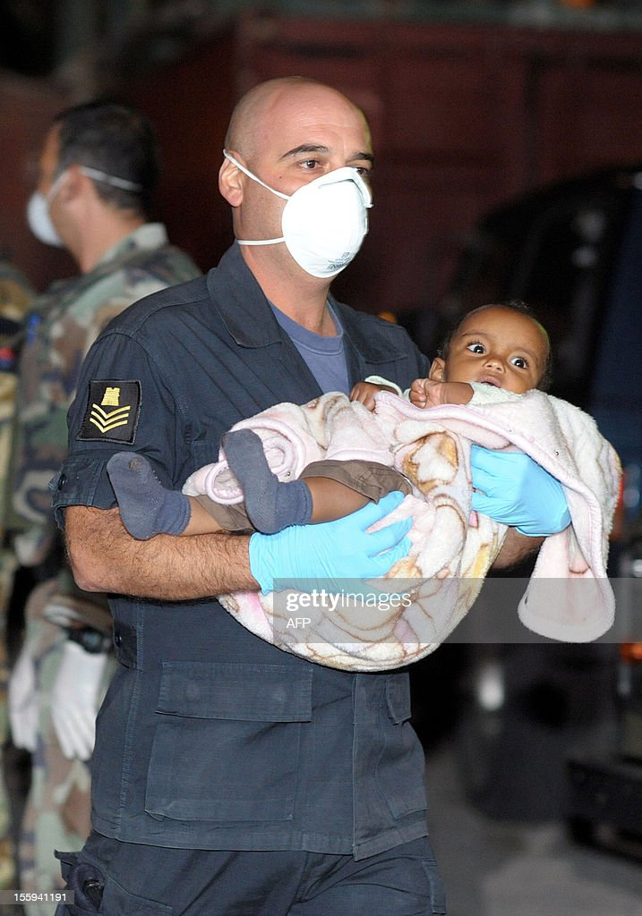 A soldier of the Armed forces of Malta soldier carries a baby off a patrol boat after a rescue operation, on November 9, 2012, in Valletta. The Maltese military rescued 250 undocumented migrants believed to be Eritrean from a stricken boat, officials said, after reports the vessel had been adrift for days. AFP PHOTO/Matthew Mirabelli -MALTA OUT-