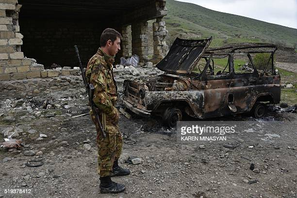 A soldier of the defense army of Nagorny Karabakh looks at a burnt out military vehicle in the village of Talish some 80km north of Karabakh's...