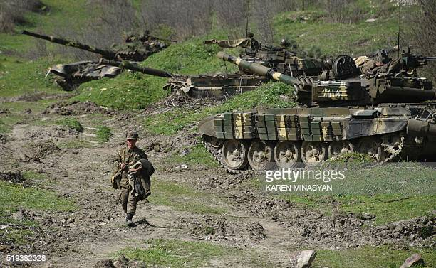 A soldier of the defense army of Nagorny Karabakh walks past tanks at a field position outside the village of Mataghis some 70km north of Karabakh's...