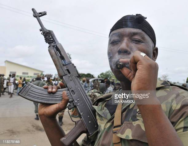 A soldier of the Forces Republicaines loyal to president Alassane Dramane Ouattara smokes a cigar before a ceremony of disarmament of militias loyal...