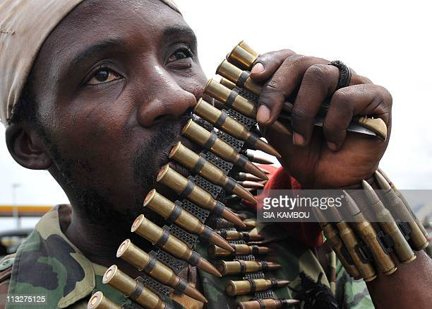 A soldier of the Forces Republicaines loyal to president Alassane Dramane Ouattara holds an ammunition belt before a ceremony of disarmament of...