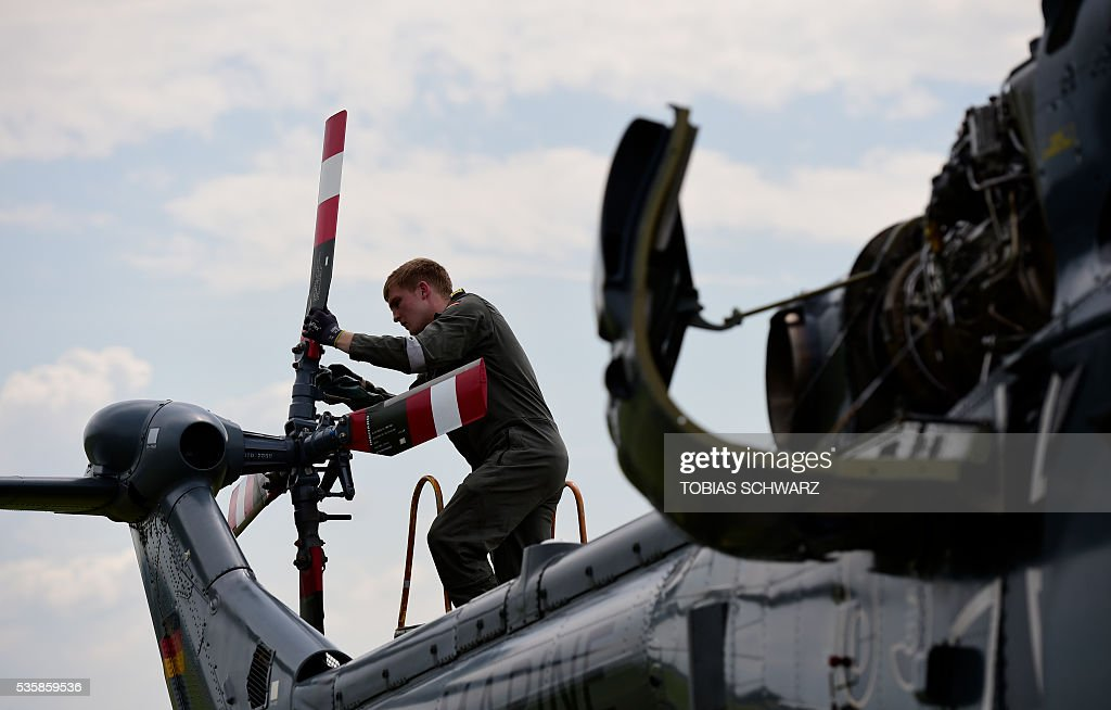 A soldier of the German Armed Forces Bundeswehr inspects the engine of a helicopter at the International Aerospace Exhibition (ILA) in Schoenefeld on May 30, 2016. The Aerospace Exhibition at Schoenefeld Airport near Berlin takes place from June 1 till 4. / AFP / TOBIAS