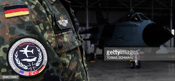 A soldier of the German Armed Forces Bundeswehr wears a badge of the combat wing Counter DAESH Incirlik next to a German Tornado jet in a hangar...