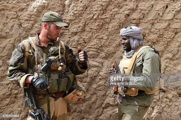 A soldier of the Malian Army Forces and a soldier of the French 93rd Mountain Artillery Regiment talk on June 3 2015 in Goundam in the Timbuktu...