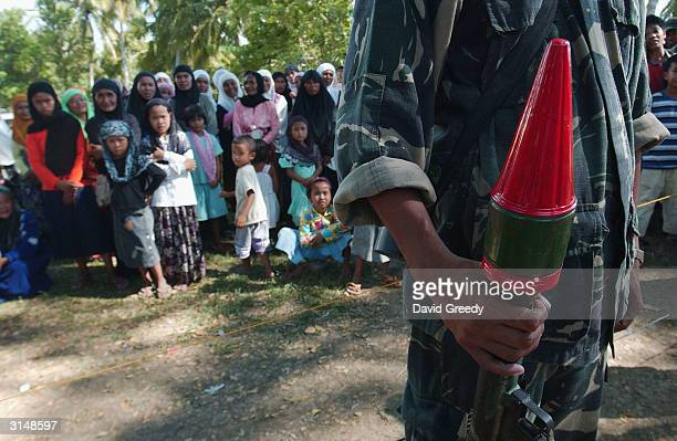 A soldier of the Moro Islamic Liberation Front holds a rocket propelled grenade as children muslim children look on at a camp in Tolitay on March 28...