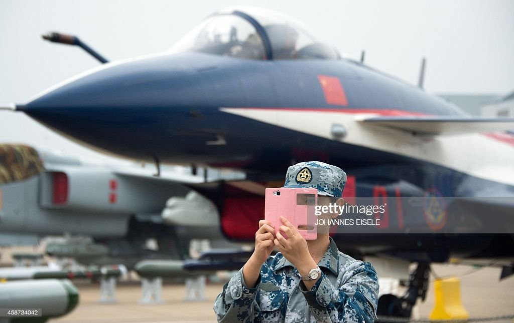 A soldier of the People's Liberation Army Air Force takes a selfie in front of a J10 jet fighter ahead of the Airshow China 2014 in Zhuhai south...