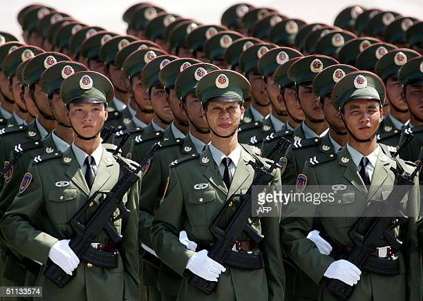 A soldier of the People's Liberation Army of China reacts as sweat gets into his eyes on a hot sunny morning as they take part in a military parade...