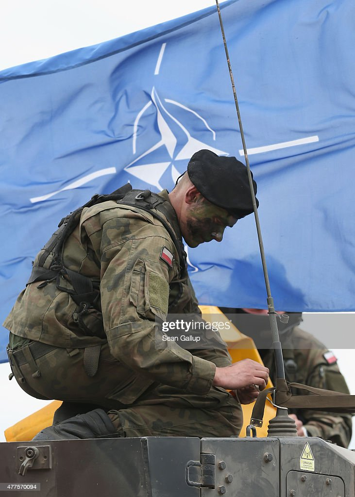 A soldier of the Polish Army mans a tank as a NATO flag flies behind during the NATO Noble Jump military exercises of the VJTF forces on June 18 2015...
