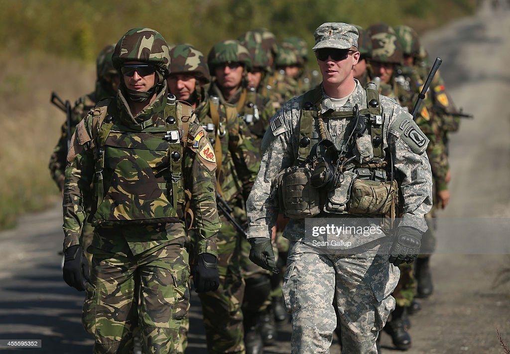 A soldier of the US Army walks with Romanian soldiers on the third day of the 'Rapid Trident' bilateral military exercises between the United States...