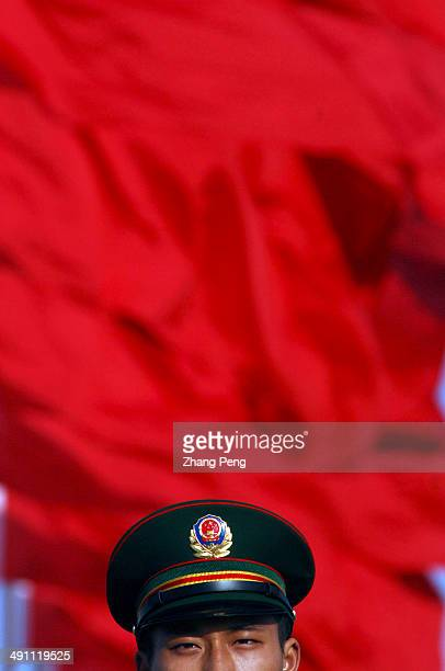 A soldier on guard duty stands under flags in Tienanmen Square which is regarded as the center of Chinese politics