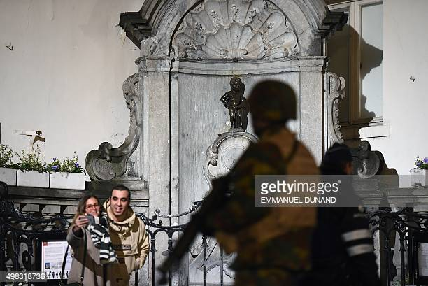 A soldier patrols around a security perimeter next to tourists taking a photo of the Manneken Pis statue as a reported police intervention takes...