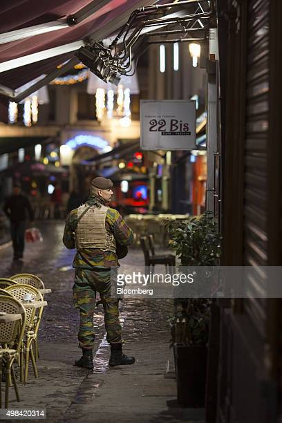 A soldier patrols at a restaurant terrace near Grand Place square in Brussels Belgium on Sunday Nov 22 2015 The search for a key suspect in the Paris...
