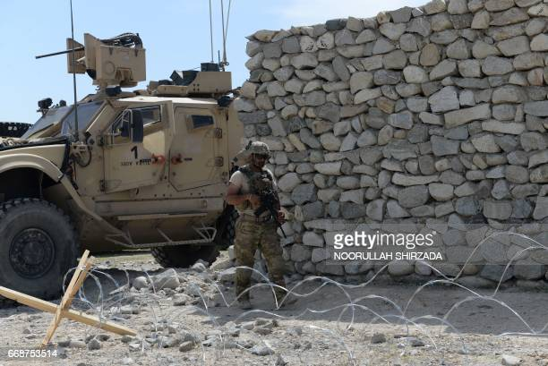 A US soldier patrols near the site of a US bombing during an operation against Islamic State militants in the Achin district of Nangarhar province on...