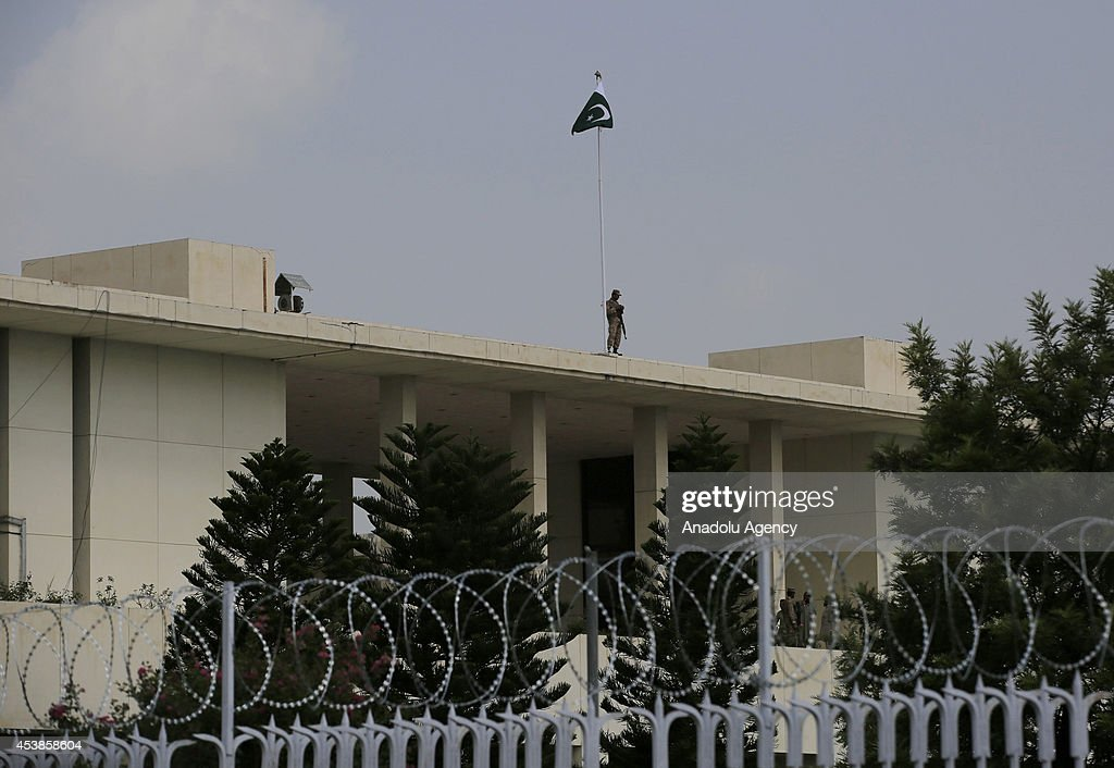 A soldier patrols on the roof of presidency building as followers of the Pakistan Tehreek-e-Insaf (PTI) and the Pakistan Awami Tehreek (PAT) parties enter Pakistani capital Islamabad's sensitive Red Zone area, which houses state buildings, on August 20, 2014. Thousands of protesters loyal to opposition politician Imran Khan and religious scholar Dr Tahir-ul-Qadri started their march on the parliament house after the two leaders asked their supporters to enter the Red Zone, a heavily protected area where many official and diplomatic buildings are located.