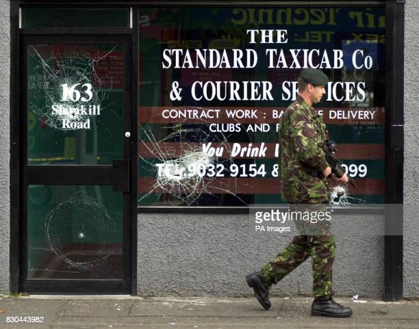 A soldier patrols outside a taxi company with smashed windows on the Shankill Road in Belfast after the British Government ordered troops back into...