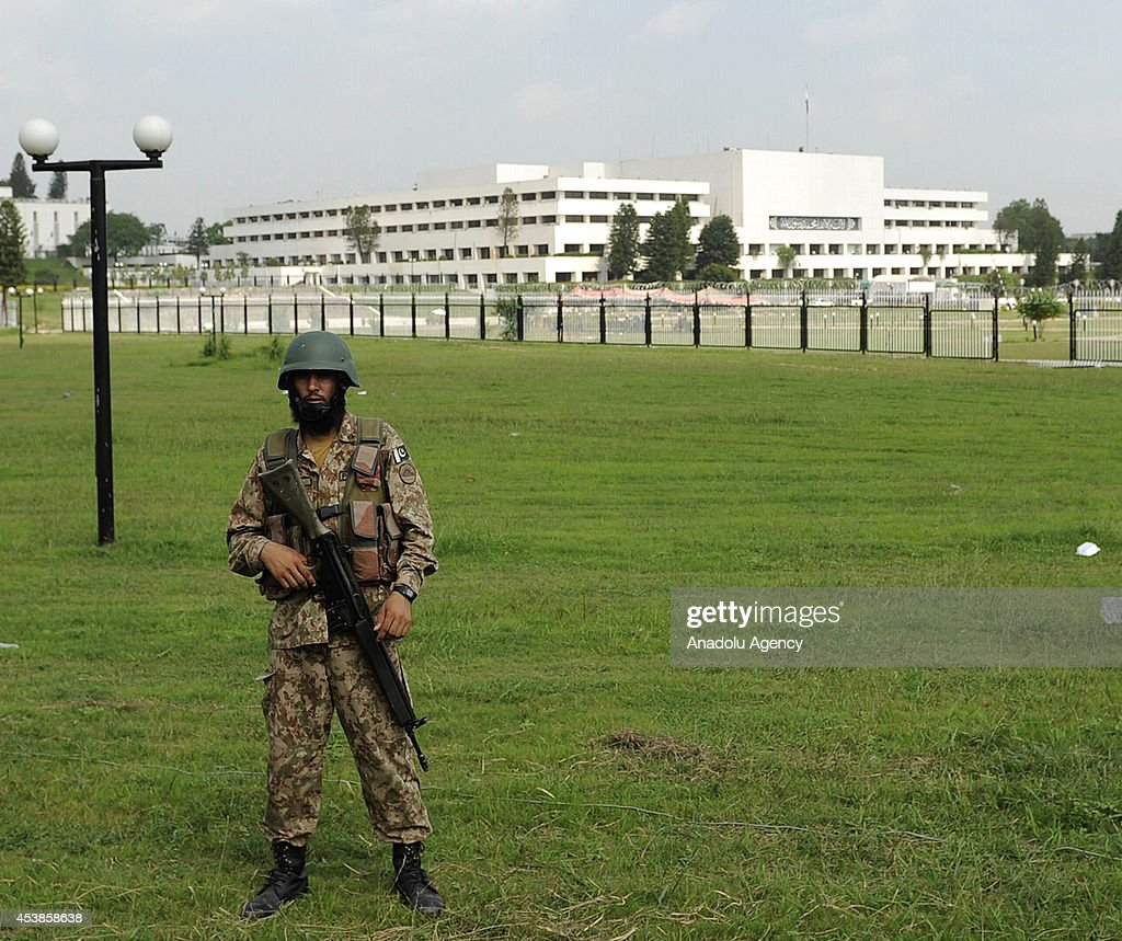 A soldier patrols outside the parliament building as followers of the Pakistan Tehreek-e-Insaf (PTI) and the Pakistan Awami Tehreek (PAT) parties enter Pakistani capital Islamabad's sensitive Red Zone area, which houses state buildings, on August 20, 2014. Thousands of protesters loyal to opposition politician Imran Khan and religious scholar Dr Tahir-ul-Qadri started their march on the parliament house after the two leaders asked their supporters to enter the Red Zone, a heavily protected area where many official and diplomatic buildings are located.