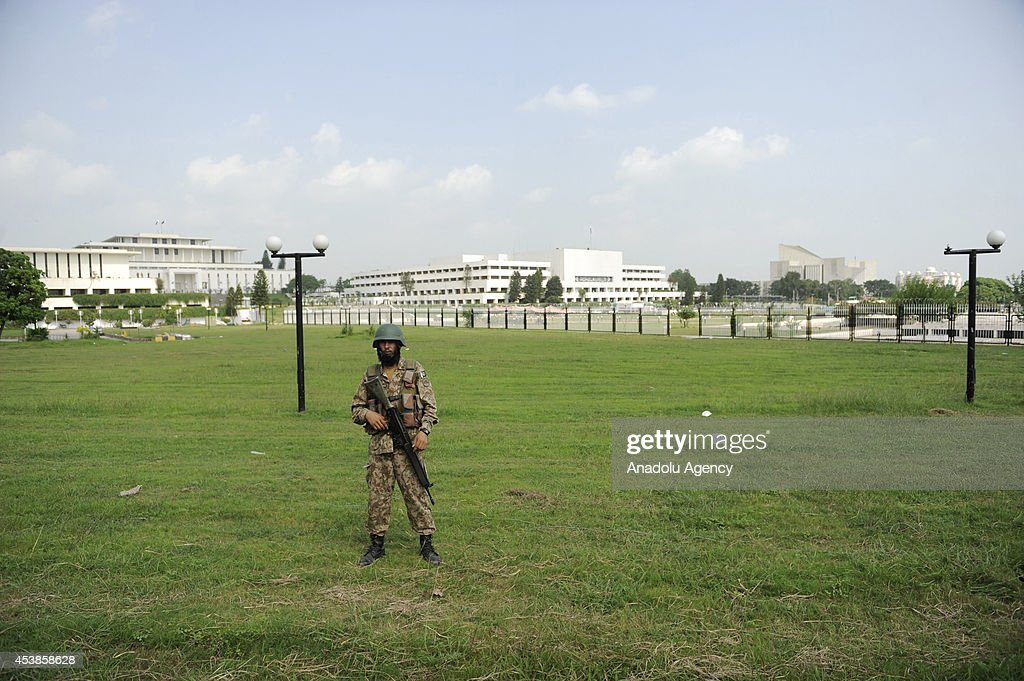 A soldier patrols outside the presidency and parliament buildings as followers of the Pakistan Tehreek-e-Insaf (PTI) and the Pakistan Awami Tehreek (PAT) parties enter Pakistani capital Islamabad's sensitive Red Zone area, which houses state buildings, on August 20, 2014. Thousands of protesters loyal to opposition politician Imran Khan and religious scholar Dr Tahir-ul-Qadri started their march on the parliament house after the two leaders asked their supporters to enter the Red Zone, a heavily protected area where many official and diplomatic buildings are located.