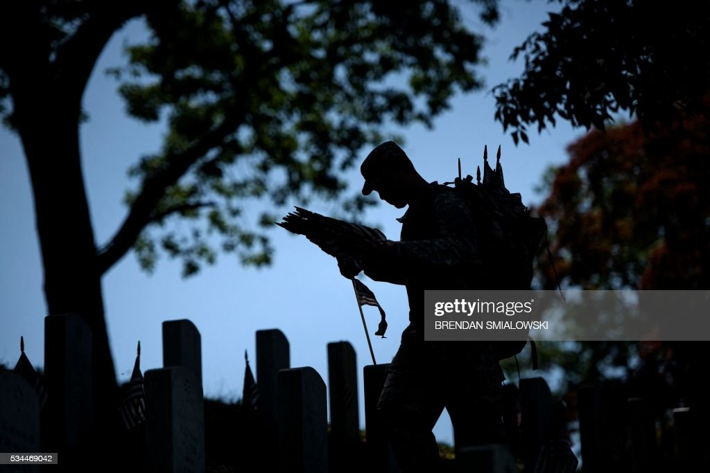 A soldier places American flags at graves in Arlington National Cemetery on May 26, 2016 in Arlington, Virginia in preparation for Memorial Day. / AFP / Brendan Smialowski