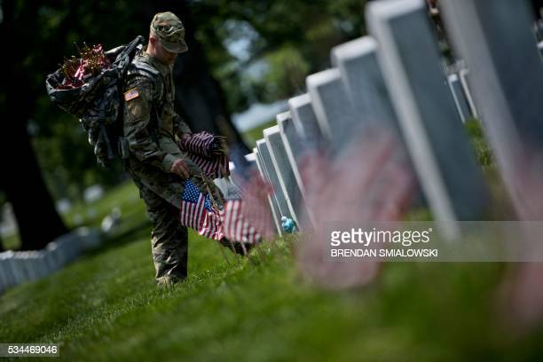 A soldier places American flags at graves in Arlington National Cemetery on May 26 2016 in Arlington Virginia in preparation for Memorial Day / AFP /...