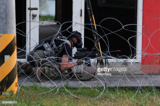 A US soldier playing the role of enemy combatant crouches behind barbed wire during Warrior Strike VIII a bilateral training exercise between the US...