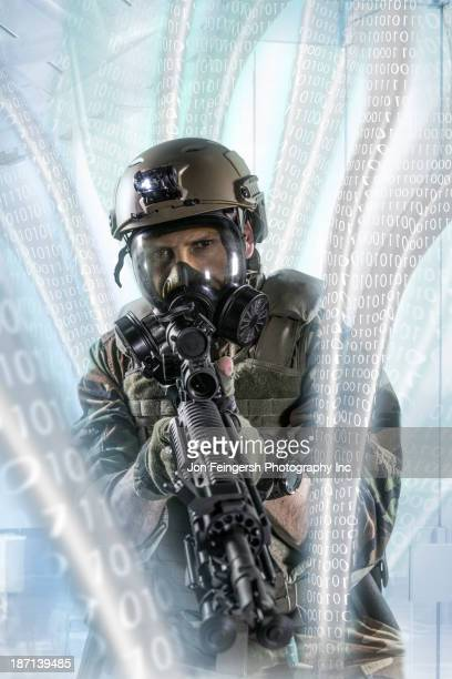 Soldier pointing gun at illuminated holograms