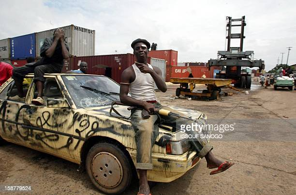 soldier poses for a photographer while civilians steal food from containers 13 August 2003 in Monrovia port Liberia Thousands of Liberians looted...